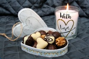 A scented candle and box of chocolate are one of the ideas for housewarming gift.