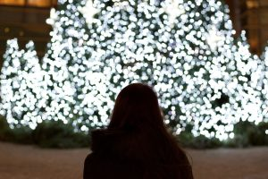 A woman taking a look at a Christmas tree