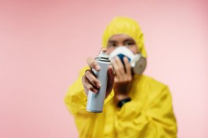 Man in overalls holding a spray