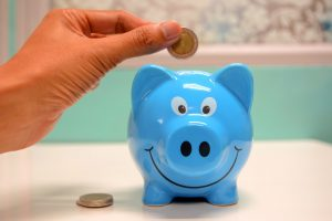 Person putting a coin in blue piggy bank